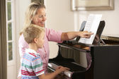 Boy in lesson with piano teacher — Stock Photo
