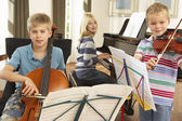 Children playing musical instruments at home — Stock Photo