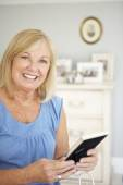 Senior woman with photographs — Stock Photo