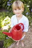 Girl watering garden — Stock Photo