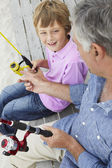 Man fishing with grandson — Stock Photo
