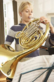 Girl playing French horn — Stock Photo