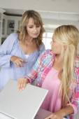 Mother supervising daughter using laptop — Stock Photo