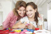 Girl doing handicrafts with grandmother — Stock Photo