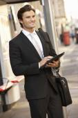 Businessman standing at bus stop — Stock Photo