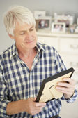 Senior man with photographs — Stock Photo