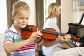 Young boy playing violin accompanied by teacher — Stock Photo