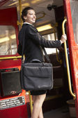 Businesswoman standing on bus platform — Foto Stock