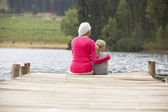 Grandmother and granddaughter on a jetty — Stock Photo