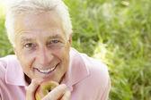Senior man eating apple — Stock Photo
