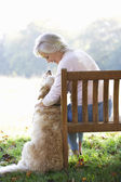 Senior woman sitting  with dog — ストック写真