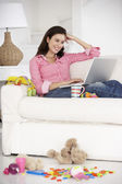 Busy mother with laptop — Stock Photo