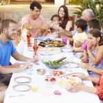 Large Family Enjoying Meal On Terrace — Stock Photo #64582867