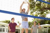 Unga män spelar volleyboll — Stockfoto