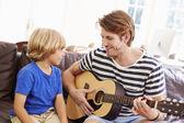 Padre con il figlio suonare la chitarra — Foto Stock