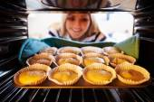 Woman Putting Cupcakes To Bake — Stock Photo