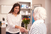 Receptionist Greeting Female Patient — Stock Photo