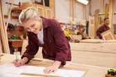 Female Apprentice Working With Plans — Stock Photo