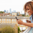 Woman Using Mobile Phone On Rooftop — Stock Photo #68250259