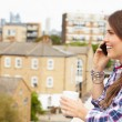Woman Using Mobile Phone On Rooftop — Stock Photo #68250677