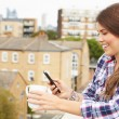 Woman Using Mobile Phone On Rooftop — Stock Photo #68251667