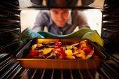 Adam sebze fırına koyarak — Stok fotoğraf