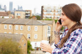 Woman Using Mobile Phone On Rooftop — Stock Photo