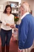 Receptionist Greeting Senior Male Patient — Stock Photo