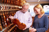 Salesman Advising Customer Violin — Stock Photo