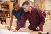 Carpenter With Apprentice Looking At Plans — Stock Photo