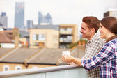 Couple On Rooftop Drinking Coffee — Stock Photo