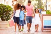 Familjen promenader med kassar och påsar — Stockfoto