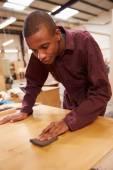 Apprentice Finishing Wood In Workshop — Stock Photo