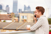 Man Using Mobile Phone On Rooftop — Stock Photo