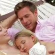 Parents cuddling daughter  in hammock. — Stock video #71415435