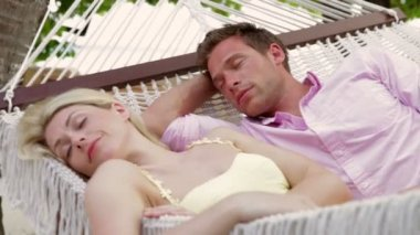Couple relaxing in hammock with eyes closed. — Vidéo
