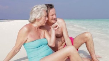 Senior couple sit at water's edge — Vidéo