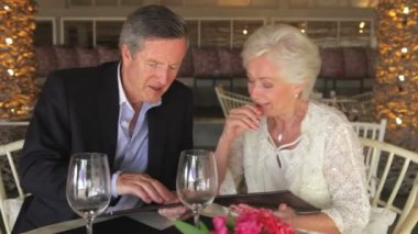Senior couple looking at menus in restaurant — Vidéo