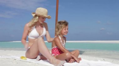 Mother puts on spray on sunscreen onto daughter — Stock Video