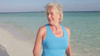 Senior woman as she walks along  beach — Vídeo de stock