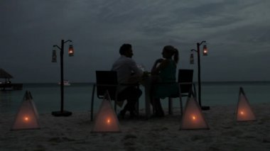 Couple enjoying evening meal at beach restaurant. — Stockvideo