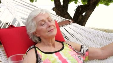 Senior woman lying in hammock — Vidéo