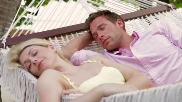 Couple relaxing in hammock with eyes closed. — Vídeo de stock
