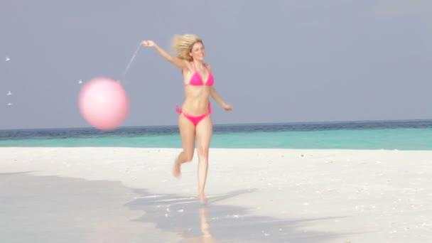 Woman as she runs along beach — Vidéo