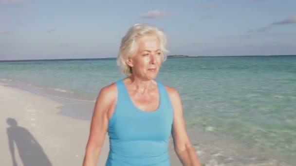 Woman as she walks along beautiful beach — Vidéo