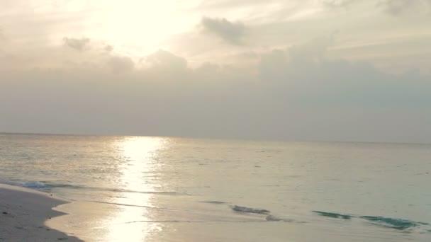 Waves breaking on empty beach as sun sets. — Vídeo de stock