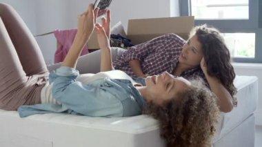 搬入新屋使用数字平板的两个女人 — 图库视频影像