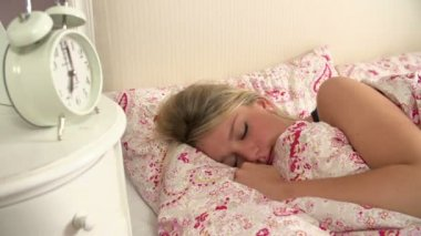 Teenage girl woken by alarm clock — Stok video