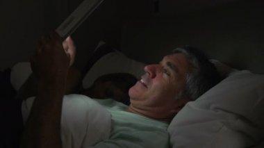 Mann mit Tablettcomputer im Bett — Stockvideo