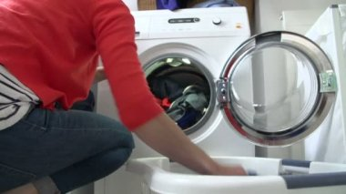 Slow Motion Of Woman Loading Clothes Into Washing Machine — Stock Video